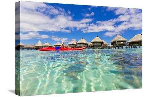 A Woman Kayaking in the Ocean at a Resort with Over-The-Water Bungalows-Mike Theiss-Stretched Canvas Print