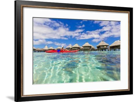 A Woman Kayaking in the Ocean at a Resort with Over-The-Water Bungalows-Mike Theiss-Framed Art Print