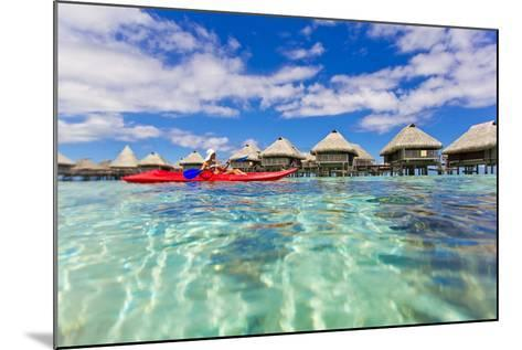 A Woman Kayaking in the Ocean at a Resort with Over-The-Water Bungalows-Mike Theiss-Mounted Photographic Print