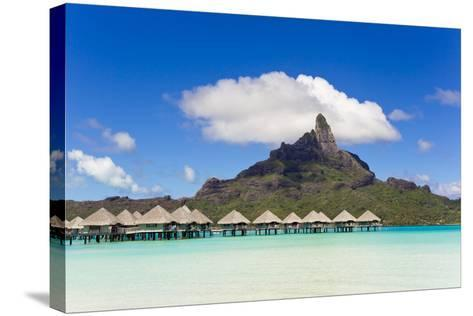 Bungalows on Stilts in a Lagoon with Mount Otemanu in the Near Distance-Mike Theiss-Stretched Canvas Print