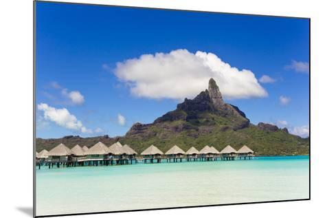 Bungalows on Stilts in a Lagoon with Mount Otemanu in the Near Distance-Mike Theiss-Mounted Photographic Print