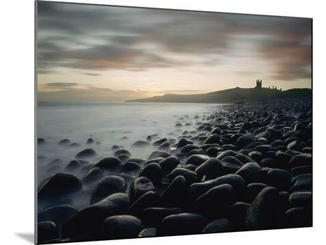 Looking Along Boulder Covered Beach Towards Dunstanburgh Castle at Dawn-Design Pics Inc-Mounted Photographic Print