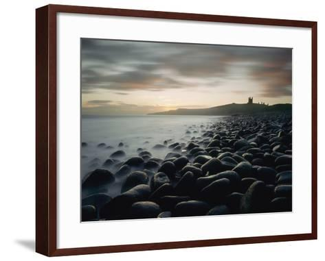 Looking Along Boulder Covered Beach Towards Dunstanburgh Castle at Dawn-Design Pics Inc-Framed Art Print