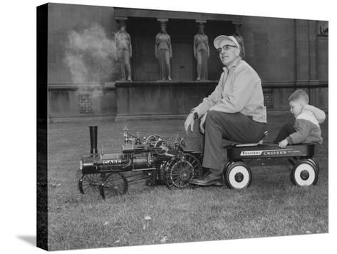 A Man and Young Boy Ride in a Wagon Being Pulled by a Model 'Case' Locomotive--Stretched Canvas Print
