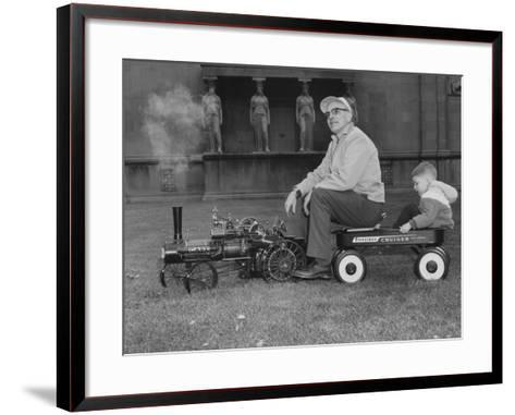 A Man and Young Boy Ride in a Wagon Being Pulled by a Model 'Case' Locomotive--Framed Art Print
