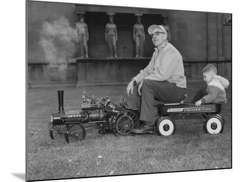 A Man and Young Boy Ride in a Wagon Being Pulled by a Model 'Case' Locomotive--Mounted Photographic Print