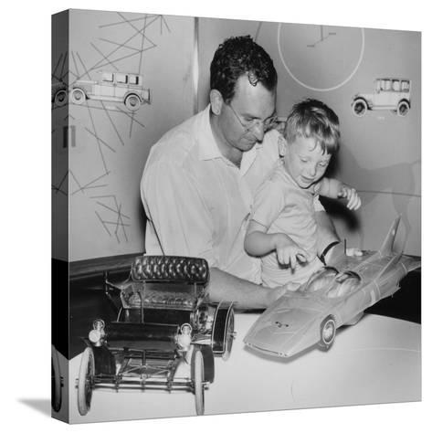 A Father Shows His Son Two Model Cars from General Motors--Stretched Canvas Print