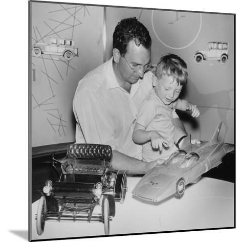 A Father Shows His Son Two Model Cars from General Motors--Mounted Photographic Print