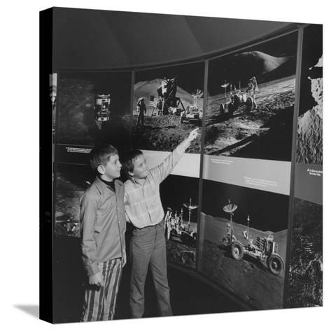 Two Young Boys Looking at Images of a Moon Landing--Stretched Canvas Print