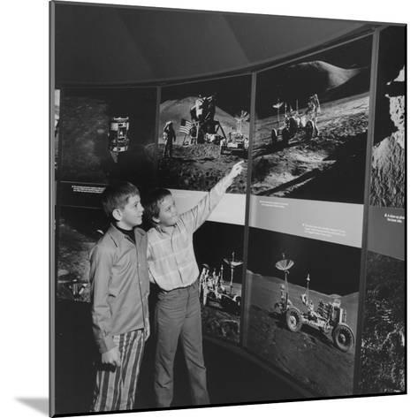 Two Young Boys Looking at Images of a Moon Landing--Mounted Photographic Print