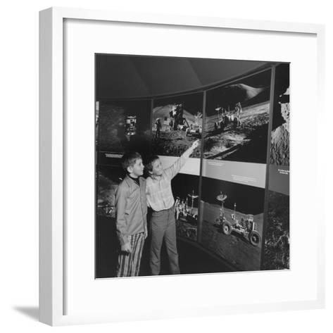 Two Young Boys Looking at Images of a Moon Landing--Framed Art Print