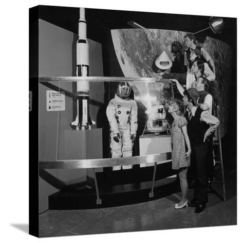 A Group of People Pose on a Ladder in Front of the NASA Apollo Exhibit--Stretched Canvas Print