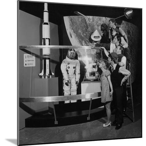 A Group of People Pose on a Ladder in Front of the NASA Apollo Exhibit--Mounted Photographic Print