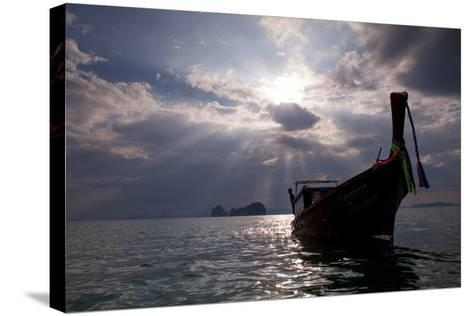Andaman Sea: A Man Leans Off of a Long Tail Boat in the Andaman Sea under Rays of Light-Ben Horton-Stretched Canvas Print