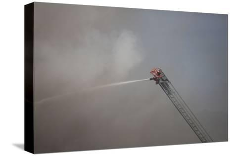 A Firefighter Battles a Fire from the Top of a Ladder Truck-Ben Horton-Stretched Canvas Print