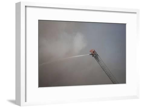 A Firefighter Battles a Fire from the Top of a Ladder Truck-Ben Horton-Framed Art Print