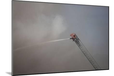 A Firefighter Battles a Fire from the Top of a Ladder Truck-Ben Horton-Mounted Photographic Print