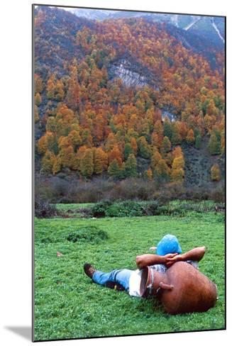 A Hiker Relaxes with His Head on an Urn, and a View of Autumn Colors in the Dohezar Forest-Babak Tafreshi-Mounted Photographic Print