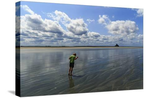 A Boy Walking Against the Wind on the Sea Floor at Mont Saint Michel Bay-Babak Tafreshi-Stretched Canvas Print