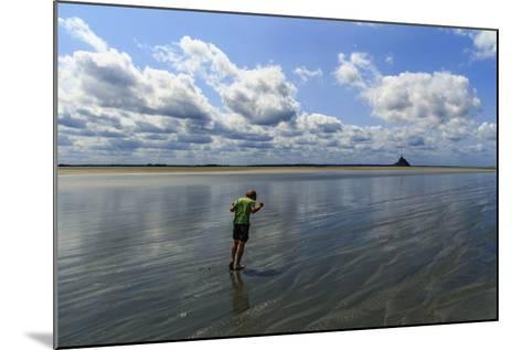 A Boy Walking Against the Wind on the Sea Floor at Mont Saint Michel Bay-Babak Tafreshi-Mounted Photographic Print