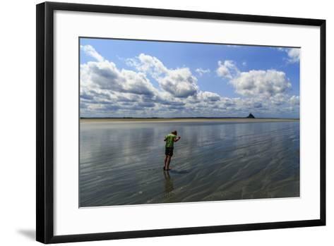 A Boy Walking Against the Wind on the Sea Floor at Mont Saint Michel Bay-Babak Tafreshi-Framed Art Print