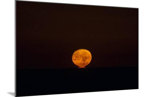 The Nearly Full Moon, Distorted by Atmospheric Refraction, Appearing to Sink into the Atlantic-Babak Tafreshi-Mounted Photographic Print