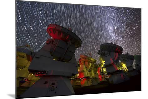 A Time-Exposure Image of Star Trails over the Alma Radio Telescopes, 5000 Meters High in the Andes-Babak Tafreshi-Mounted Photographic Print