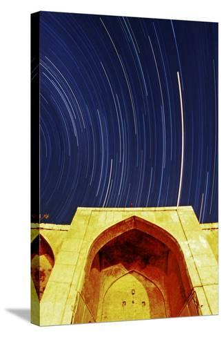 A Time-Exposure of Star Trails Above a Historic Caravansary. the Brightest Trail Is Planet Mars-Babak Tafreshi-Stretched Canvas Print