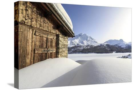 The Sun, Covered by Thin Clouds, Illuminating a Typical Hut Covered with Snow at the Maloja Pass-Roberto Moiola-Stretched Canvas Print