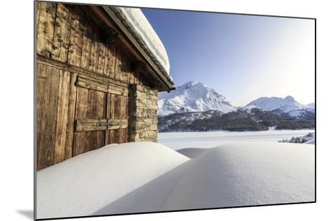 The Sun, Covered by Thin Clouds, Illuminating a Typical Hut Covered with Snow at the Maloja Pass-Roberto Moiola-Mounted Photographic Print