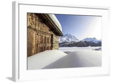 The Sun, Covered by Thin Clouds, Illuminating a Typical Hut Covered with Snow at the Maloja Pass-Roberto Moiola-Framed Art Print