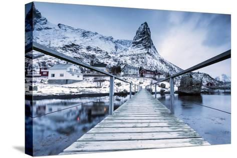 A Bridge over the Cold Sea Connects a Typical Fishing Village. Reine-Roberto Moiola-Stretched Canvas Print