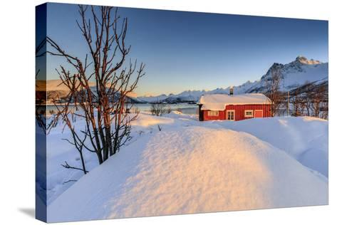 The Winter Sun Illuminates a Typical Norwegian Red House Surrounded by Fresh Snow-Roberto Moiola-Stretched Canvas Print