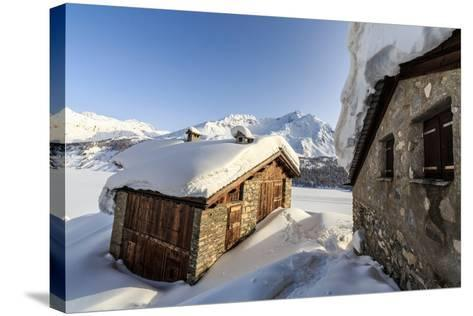 The Sun, Covered with Thin Clouds, Illuminating a Typical Hut Covered with Snow at the Maloja Pass-Roberto Moiola-Stretched Canvas Print