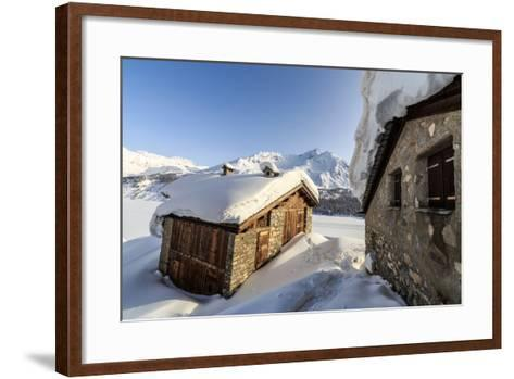 The Sun, Covered with Thin Clouds, Illuminating a Typical Hut Covered with Snow at the Maloja Pass-Roberto Moiola-Framed Art Print