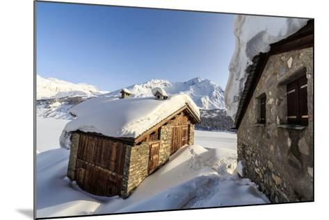 The Sun, Covered with Thin Clouds, Illuminating a Typical Hut Covered with Snow at the Maloja Pass-Roberto Moiola-Mounted Photographic Print