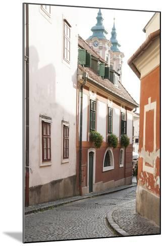 Cobblestone Street and Narrow Buildings with Church Towers in Background, Eger, Hungary-Kimberly Walker-Mounted Photographic Print