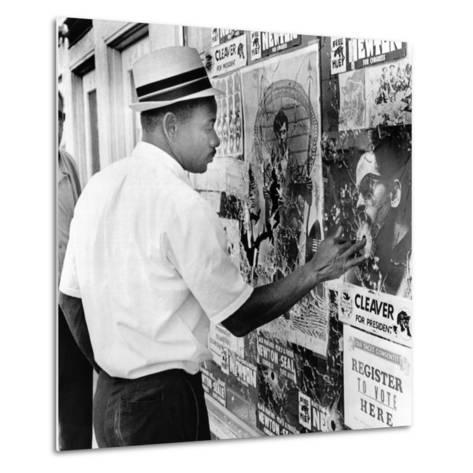 An African American Pokes His Finger into a Bullet Hole in the Oakland Black Panther's Headquarters--Metal Print