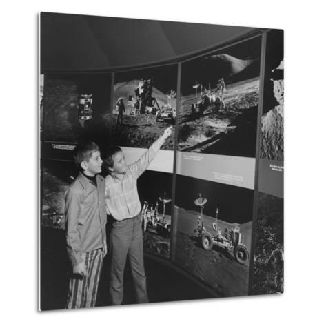 Two Young Boys Looking at Images of a Moon Landing--Metal Print