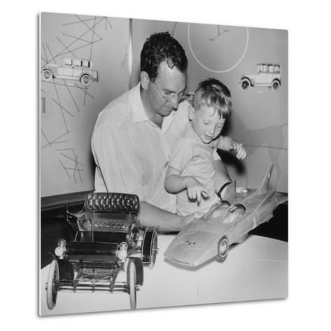 A Father Shows His Son Two Model Cars from General Motors--Metal Print