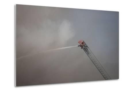 A Firefighter Battles a Fire from the Top of a Ladder Truck-Ben Horton-Metal Print