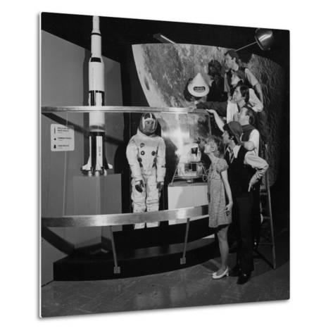 A Group of People Pose on a Ladder in Front of the NASA Apollo Exhibit--Metal Print