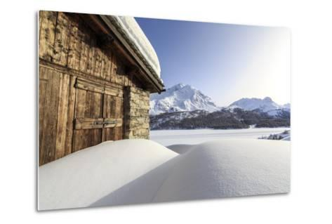 The Sun, Covered by Thin Clouds, Illuminating a Typical Hut Covered with Snow at the Maloja Pass-Roberto Moiola-Metal Print