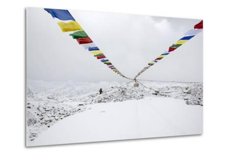 A Porter Walks by a Puja with Prayer Flag in Everest Base Camp, Nepal-Alex Treadway-Metal Print