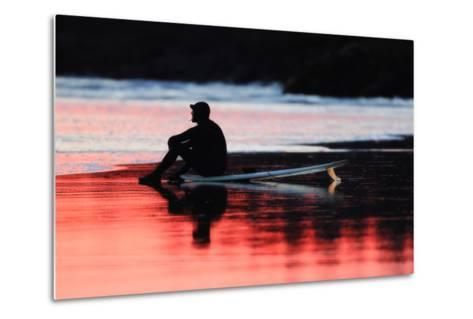 A Surfer Sits on His Surfboard While Watching the Waves at Sunset-Robbie George-Metal Print