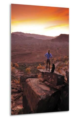 A Woman and a Dog on Top of a Rock Covered in Petroglyphs, Looking at a Beautiful Sunset-Keith Ladzinski-Metal Print
