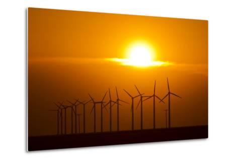 The Sun Sets Behind a Row of Spinning Windmills or Wind Turbines-Mike Theiss-Metal Print