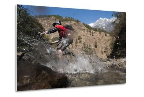A Mountain Biker Blasts Through a Stream in the Mountains of Nepal-Alex Treadway-Metal Print