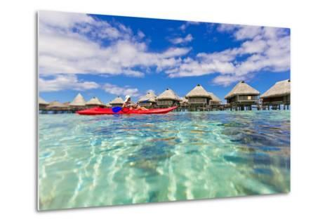 A Woman Kayaking in the Ocean at a Resort with Over-The-Water Bungalows-Mike Theiss-Metal Print