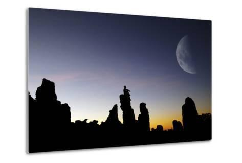 Composite Image of a Man Sitting on Top of a Small Pillar at Sunset, Looking at a Moon-Keith Ladzinski-Metal Print